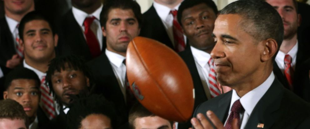 PHOTO: Barack Obama plays with a football as members of the Ohio State University Buckyes football team look on during an East Room event at the White House April 20, 2015 in Washington, DC.