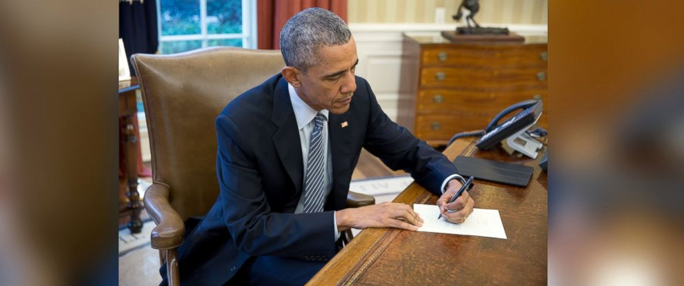 PHOTO: President Barack Obama signs a letter to Ileana Yarza, a 76-year-old letter writer in Cuba, in the Oval Office, March 14, 2016.