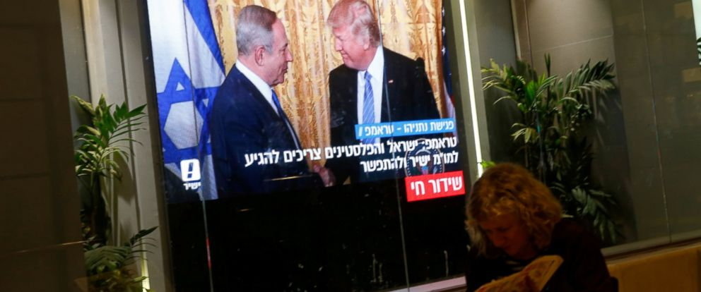PHOTO: A woman reads a newspaper as monitors showing the meeting between U.S. President Donald Trump and Israeli Prime Minister Benjamin Netanyahu in Washington, are seen next to a coffee shop in Tel Aviv, Israel, Feb. 15, 2017.