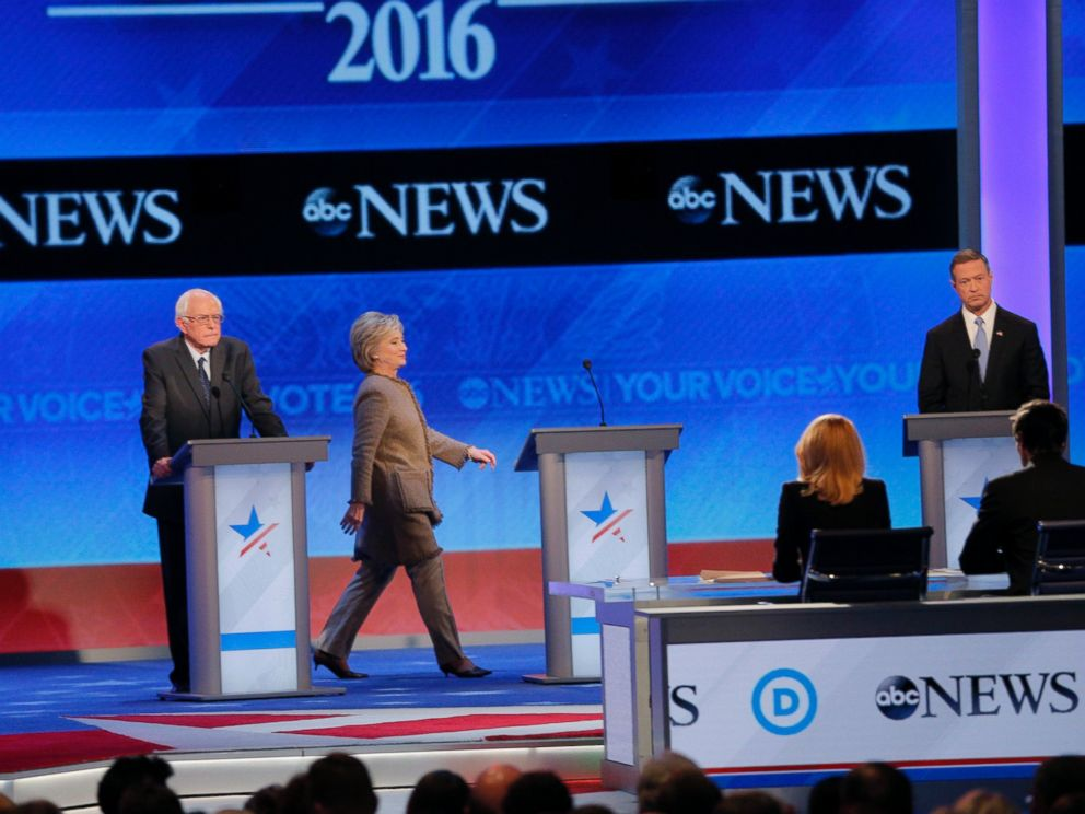 PHOTO: Hillary Clinton, center, walks to her empty podium between rivals Sen. Bernie Sanders, left, and Martin OMalley after she was late to return for the resumption of the Democratic debate at St. Anselm College in Manchester, N.H., Dec. 19, 2015.