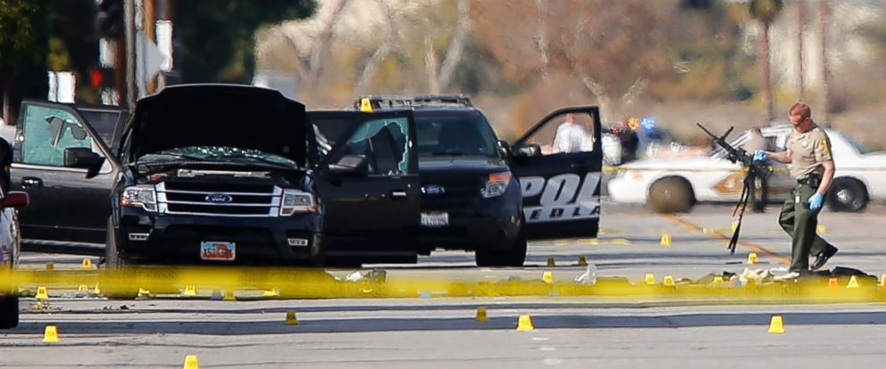 PHOTO: A police officer picks up a weapon from the scene of the investigation around the area of the SUV vehicle where two suspects were shot by police following a mass shooting in San Bernardino, Calif. Dec. 3, 2015.