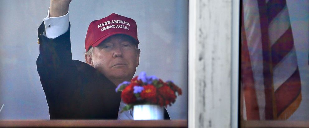 President Donald Trump waves to spectators as he watches the third round of the U.S. Womens Open Golf tournament from his observation booth, Saturday, July 15, 2017, in Bedminster, N.J. (AP Photo/Seth Wenig)