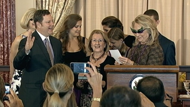 VIDEO: Clinton wears wing-tipped purple and green sunglasses to swear in Mike Hammer.
