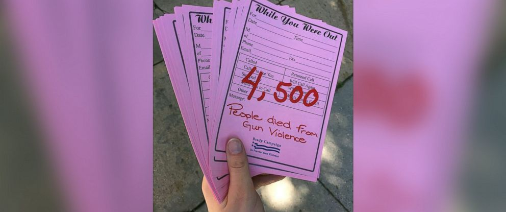 "PHOTO: A Brady Campaign volunteer holds pink ""While You Were Out"" memos for congressmen on Capitol Hill."