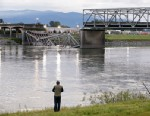 A person looks from the south bank of the Skagit River across to the collapsed portion of the Interstate 5 bridge, May 24, 2013, in Mount Vernon, Wash.