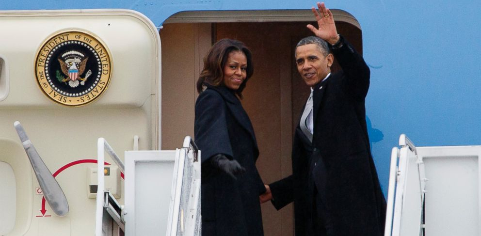 PHOTO: President Barack Obama, accompanied by first lady Michelle Obama, waves prior to boarding Air Force One at Andrews Air Force Base, Md., Monday, Dec. 9, 2013, before traveling to South Africa for a memorial service in honor of Nelson Mandela.