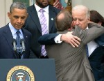 PHOTO: President Barack Obama stands at the podium at left as Mark Barden, the father of Newtown shooting victim Daniel is embraced by Vice President Joe Biden during a news conference
