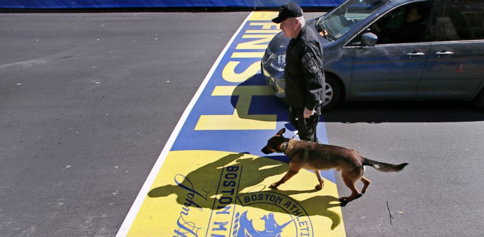 PHOTO: Boston Police officer John Quinn walks with, Miller, his bomb detection canine, over the finish line while sweeping the area in preparation for the Boston Marathon, April 16, 2014, in Boston.