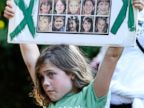 PHOTO: Marie Morosky, of Newtown, Conn. holds up a sign with images of the children killed in the Sandy Hook School shooting outside an event for Republican candidate Tom Foley with New Jersey Gov. Chris Christie, July 21, 2014, in Greenwich, Conn.