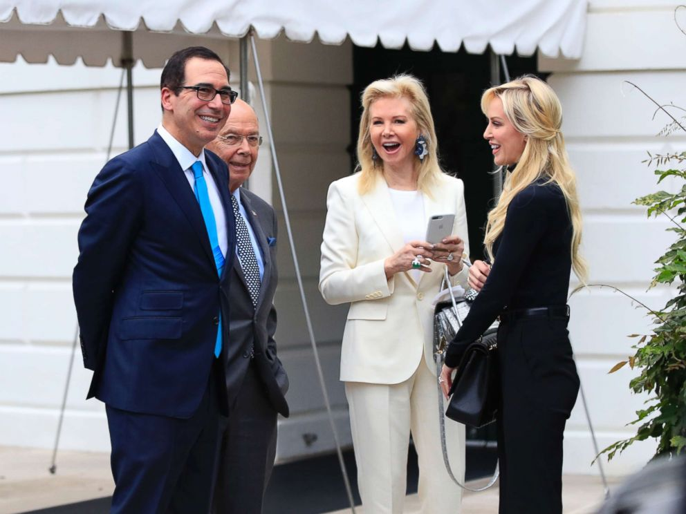 PHOTO: Treasury Secretary Steven Mnuchin, left, and his wife, Louise Linton, right, and Secretary of Commerce Wilbur Ross, second from left, and his wife Hilary Geary, second from right, wait for President Trump at the White House, July 29, 2017.