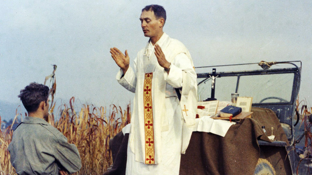 PHOTO: Father Emil Kapaun celebrates Mass using the hood of his jeep as an altar, as his assistant, Patrick J. Schuler, kneels in prayer in Korea on Oct. 7, 1950, les