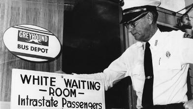 "PHOTO: Police Chief George H. Guy poses beside the ""White waiting room"" sign posted outside the Greyhound bus terminal in McComb, Mi., on Nov. 2, 1961."