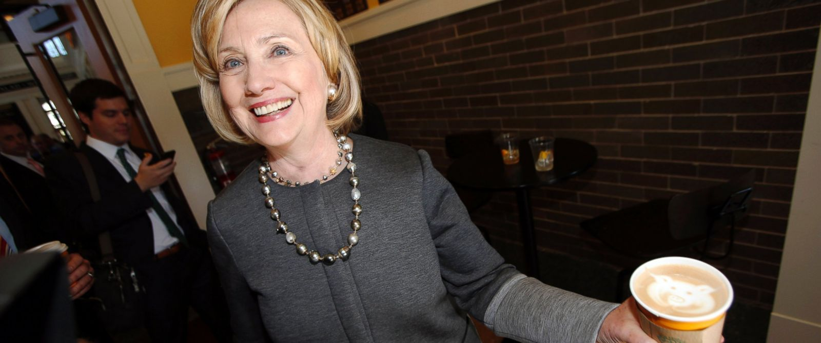 PHOTO: Hillary Clinton holds up her small white mocha latte with a logo of the coffee shop drawn in the foam as she campaigns for U.S. Sen. Mark Udall, during a stop in the newly-renovated Union Station in Denver on Oct. 13, 2014.