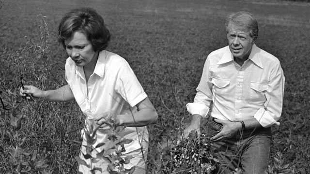 PHOTO: President Jimmy Carter carries a peanut plant as he follows his wife Rosalynn from the field at their Webster County, Ga., farm on Aug. 19, 1978.