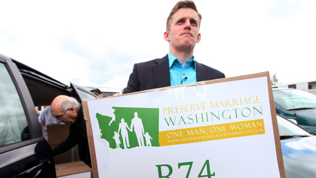 PHOTO: Joseph Backholm, the chair of Preserve Marriage Washington, carries one of the first boxes of petitions for Referendum 74 into the Secretary of State's office to stop Washington's gay marriage law, June 6, 2012, in Olympia, Wash.