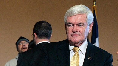 PHOTO: Newt Gingrich, pauses as an unidentified protester is confronted by security during a news conference.