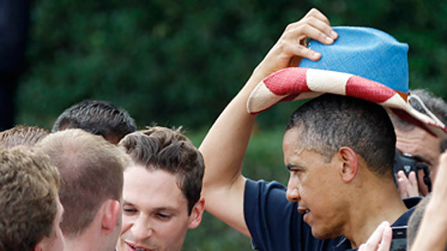 PHOTO: President Barack Obama puts on a red, white, and blue hat, while visiting with service members during the Independence Day celebration in Washington, July 4, 2012.