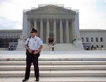 A police officer keeps watch outside the Supreme Court in Washington, June 17, 2013.