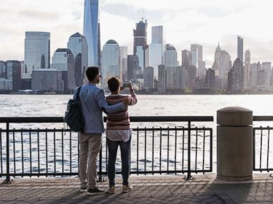 PHOTO: A couple stands looking at Manhattan.