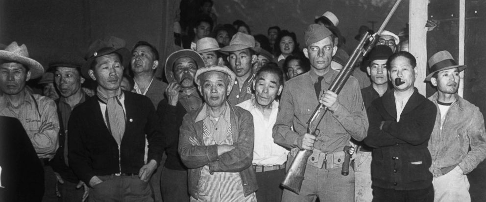 PHOTO: An American soldier guards a crowd of Japanese American internees at an internment camp at Manzanar, California during World War II.