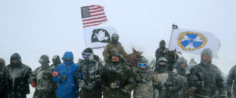"""PHOTO: Despite blizzard conditions, military veterans march in support of the """"water protectors"""" at Oceti Sakowin Camp on the edge of the Standing Rock Sioux Reservation, Dec. 5, 2016, outside Cannon Ball, North Dakota."""