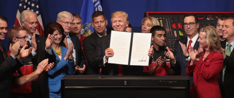 PHOTO: President Donald Trump signs an executive order to try to bring jobs back to American workers and revamp the H-1B visa guest worker program during a visit to the headquarters of tool manufacturer Snap-On on April 18, 2017 in Kenosha, Wis.