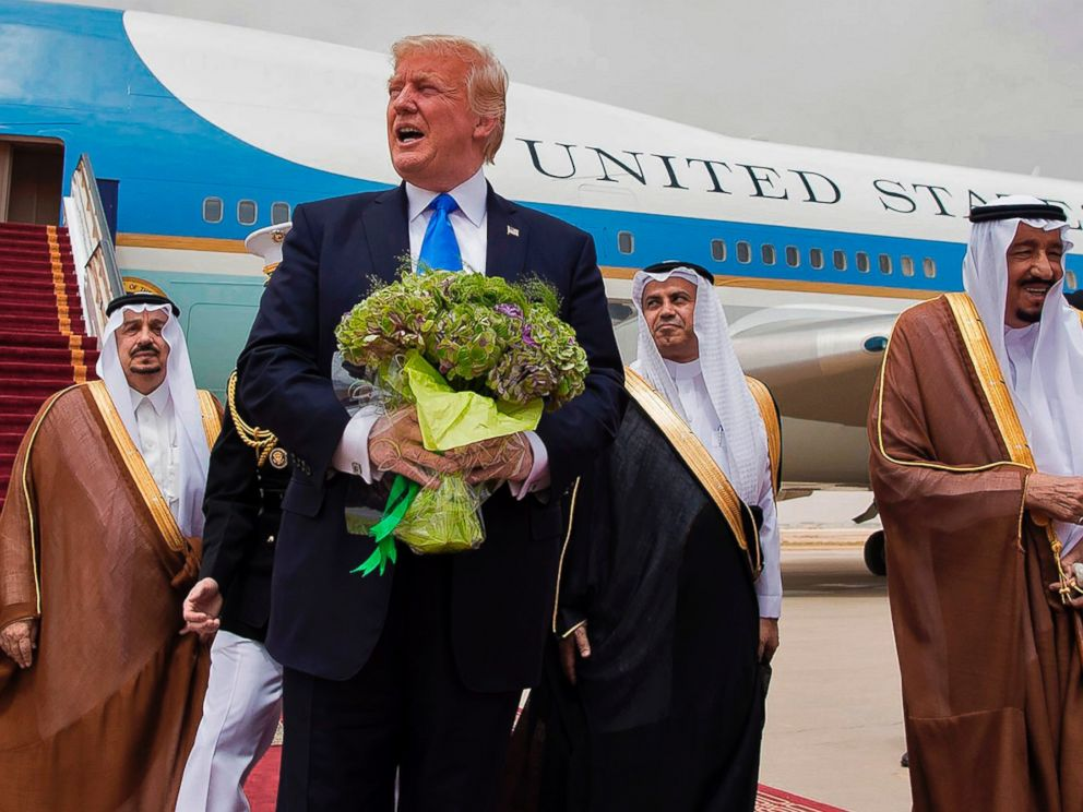 PHOTO: President Donald Trump holds a bouquet of flowers upon being welcomed by Saudi King Salman bin Abdulaziz al-Saud during his arrival at the airport in Riyadh on May 20, 2017.