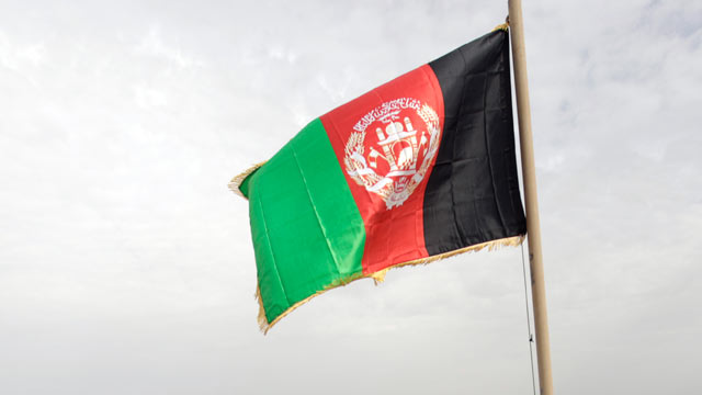 PHOTO: Afghan residents of Marjah sit at the foot of the national flag just hoisted by Helma, Feb. 25, 2010.