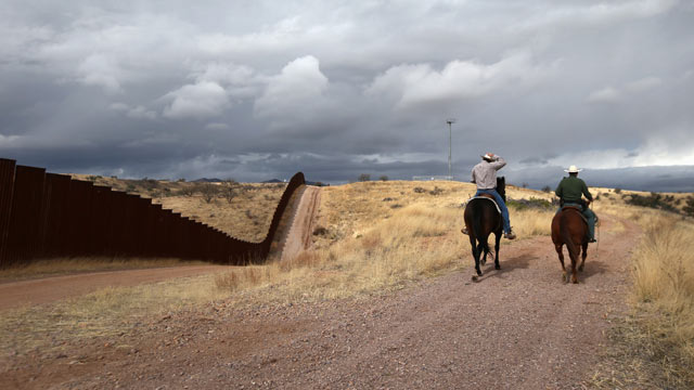 "PHOTO: U.S. Border Patrol ranch liaison John ""Cody"" Jackson (R) rides with cattle rancher Dan Bell on Bells ZZ Cattle Ranch along the U.S.-Mexico border fence on March 8, 2013 in Nogales, Ariz."