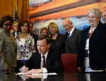 PHOTO: Colorado Governor John Hickenlooper signs three gun control measures in his office at the state capitol, March, 20, 2013.