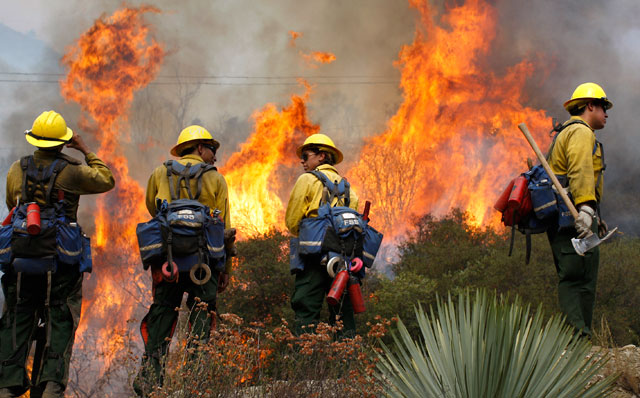 PHOTO: U.S. Forest Service firefighters stand near flames in the Angeles National Forest, Sept. 4, 2012 north of Glendora, Calif.