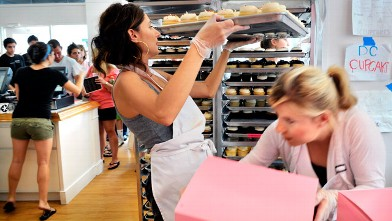 PHOTO: Katherine Kallinis, center left, and her sister Sophie LaMontagne, right, pack up cupcake orders as fast as they can in the kitchen of the extremely successful Georgetown Cupcakes on August, 11, 2010 in Washington, DC.