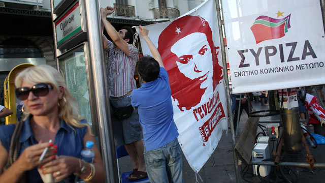 PHOTO: Supporters of the Syriza party erect a banner before a rally ahead of Sunday's general election, June 14, 2012 in Athens, Greece.