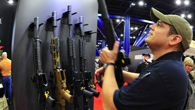 PHOTO: A convention goers picks up a weapon equipped with a silencer during the 142nd annual National Rifle Association (NRA)Convention at the George R. Brown Convention Center May 4, 2013 in Houston, Texas.