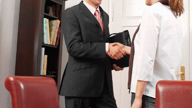 PHOTO: An insurance agent and woman shaking hands.