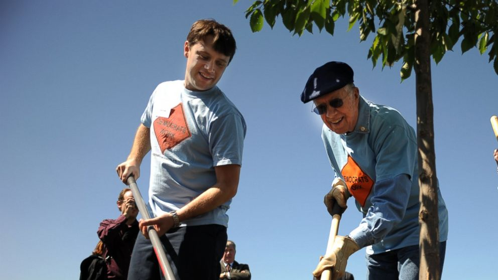 PHOTO: Former president Jimmy Carter, center, and his wife Rosalyn, right, and their grand son Jason are tree planting during their participating in the day service with the Georgia Delegation at Bicentennial Park in Aurora on August 27, 2008.