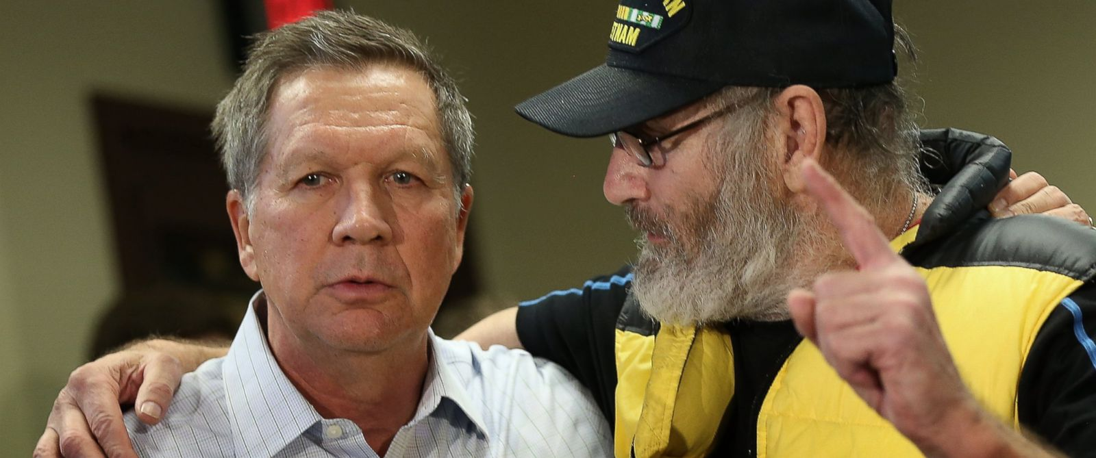 PHOTO: Vietnam veteran David AuCoin puts his arm around Republican presidential candidate John Kasich as he asks the candidate a question during a town hall event at the Plaistow Town Hall, Feb. 8, 2016 in New Hampshire.