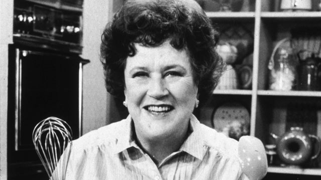 "PHOTO: American chef Julia Child stands in front of a countertop, holding a whisk and a ladle, on the set of her television series, ""The French Chef""."
