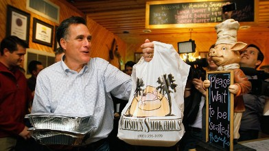 PHOTO: Republican presidential candidate, former Massachusetts Gov. Mitt Romney carries a takeout order of barbeque at Hudson's Smokehouse on January 18, 2012 in Lexington, South Carolina.