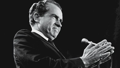 PHOTO: American President Richard Nixon holds his hands together before him around a microphone as he grins during a campaign rally at Madison Square Garden, New York, Oct. 31, 1968.