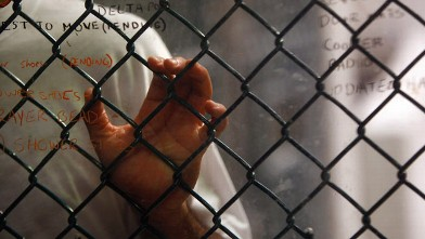 "PHOTO: A detainee stands at an interior fence at the U.S. military prison for ""enemy combatants"" October 28, 2009 in Guantanamo Bay, Cuba."