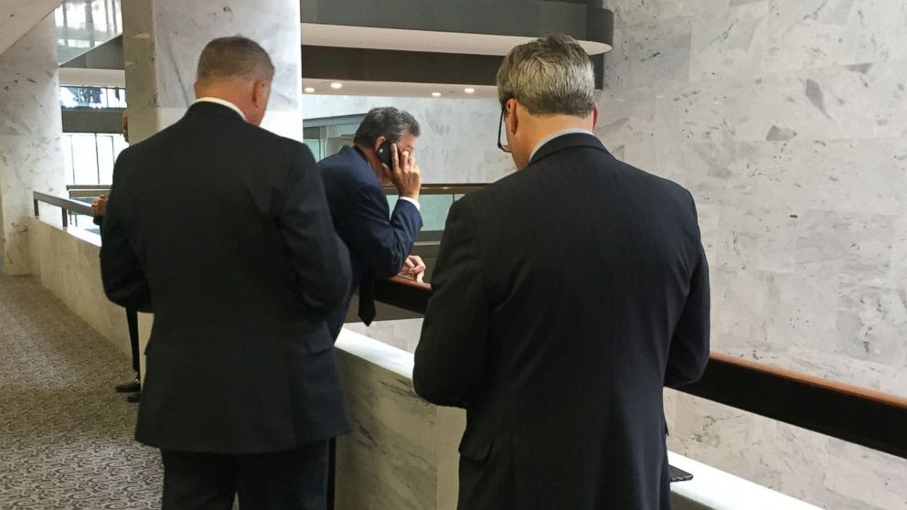 PHOTO: Sen. Joe Manchin, D-West Virginia, talks on the phone as two FBI officials wait outside of a secure room on Capitol Hill, where a classified briefing with Senators was set to begin, May 24, 2017.