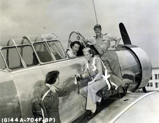 Photo of three women and a man with a plane. One woman is sitting in the pilot's seat, talking to the two women crouching by the side of the plane. The man is standing next to the women, smiling broadly at the camera.