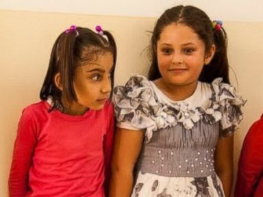 PHOTO: School girls waiting in line to be fitted for shoes provided by TentEd at Garanawa Elementary School in Erbil on July 3, 2014
