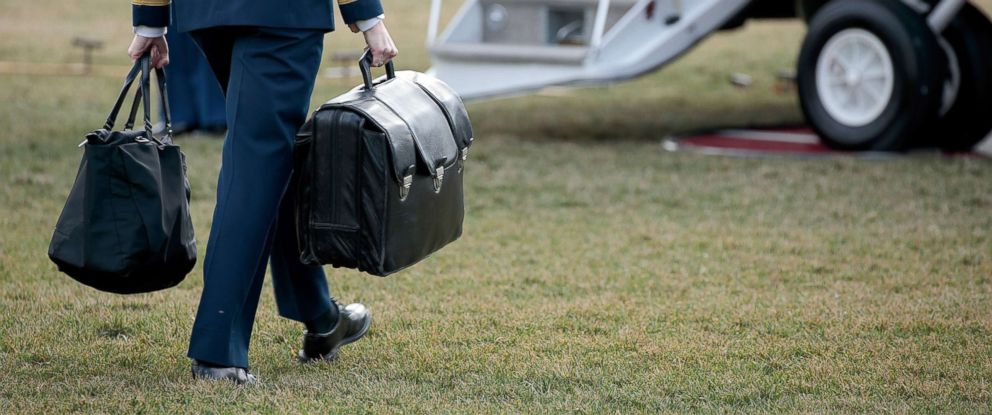 PHOTO: A military aide carries the alleged football, a case with the launch codes for nuclear weapons, toward Marine One as President Donald Trump prepares to take off on the South Lawn of the White House, Jan. 26, 2017.