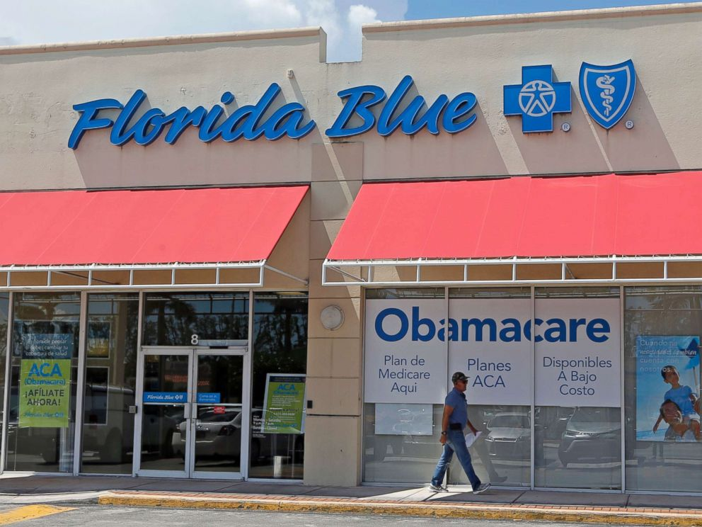 PHOTO: A person walks by a health care insurance office in Hialeah, Fla. on July 27, 2017.