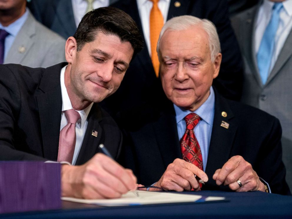 PHOTO: Speaker of the House Paul Ryan accompanied by Senate Finance Committee Chairman Orrin Hatch, right, signs the final version of the GOP tax bill during an enrollment ceremony at the Capitol in Washington, Dec. 21, 2017.