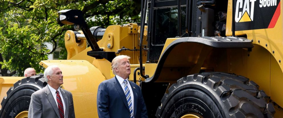 """PHOTO: President Donald Trump and Vice President Mike Pence examine an iconic Yellow Iron from Caterpillar Inc. during a """"Made in America"""" product showcase event on the South Lawn at the White House in Washington, July 17, 2017."""