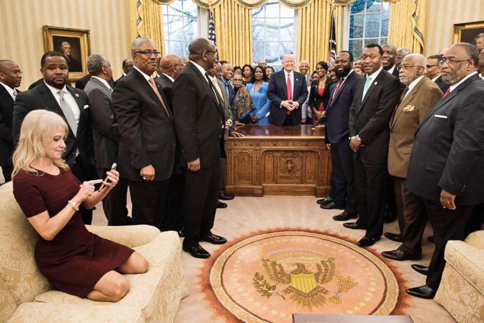 'PHOTO: Counselor to the President Kellyanne Conway (L) checks her phone after taking a photo as President Donald Trump and leaders of historically black universities and colleges pose for a group photo in the Oval Office of the White House, Feb. 27, 2017.' from the web at 'http://a.abcnews.com/images/Politics/trump-university-heads-gty-jpo-171215_3x2_992.jpg'