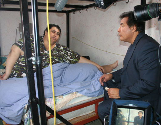 Pic: ABC's John Quinones at Manuel Uribe's bedside in late 2006, when he was several hundred pounds heavier than he is today.